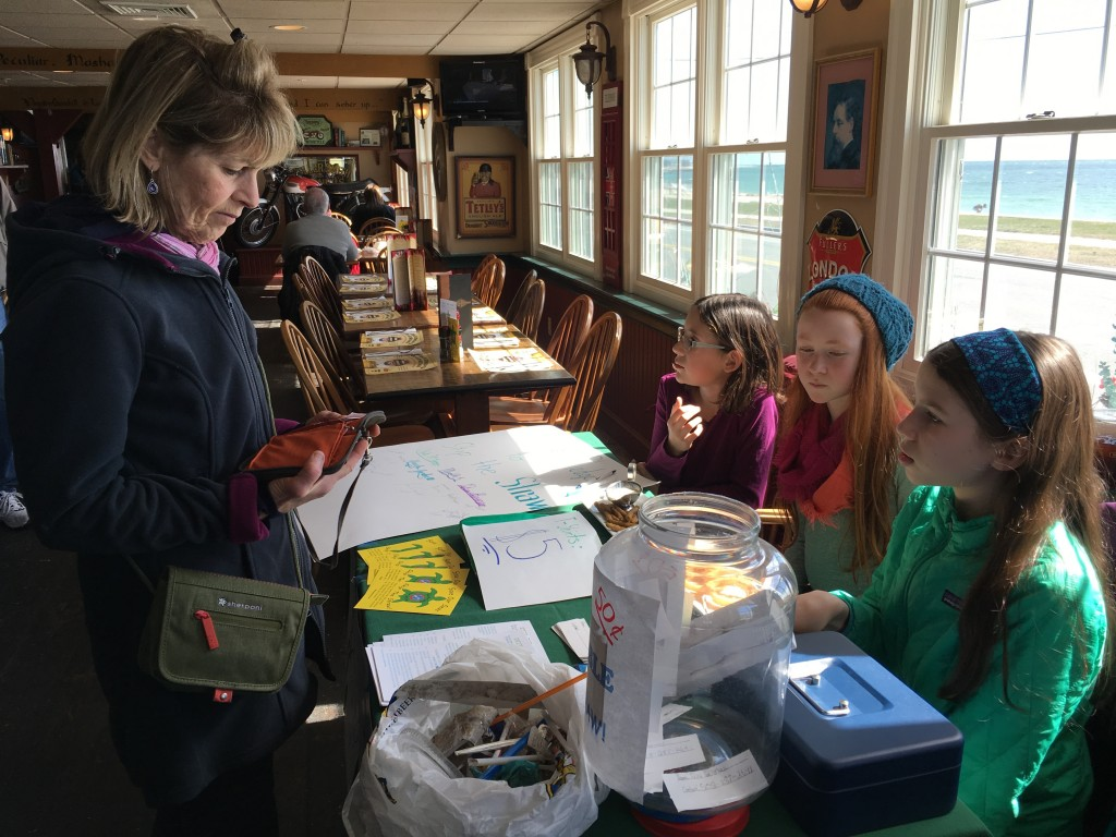 Meredith Kinkade, Sadie Leveque, and Petra Brienza explain the problems with single-use plastics like straws to customers at the British Beer Company during the recent Polar Plunge.